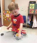 Using the scale to try and balance pebbles and rocks on each side